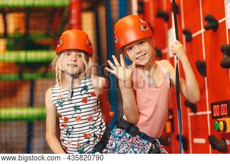 Indoor Climbing Class For Kids. School Girls Smiling At The Camera And Having Fun In Indoor Playgrou
