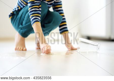 Little Boy Wipes Water Spilled From A Glass On The Floor. Teaching A Child To Clean Up After Himself