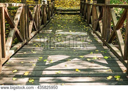 Wooden Bridge Over The Stream In The Park.
