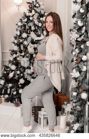 Close Up Of Happy Smiling Pregnant Woman Touching Her Belly Over Christmas Tree Background