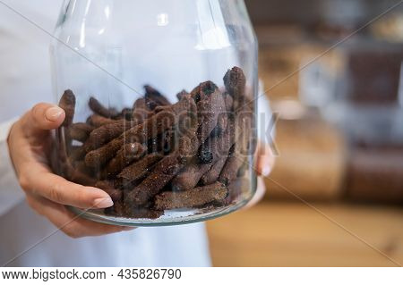A Woman Holds Croutons In A Glass Jar. Eco Shop Without Plastic Waste.