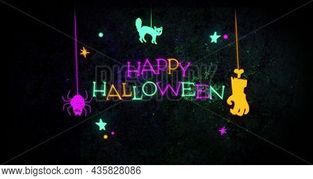 Image of neon Happy Halloween text and decoration with hanging spider, cat and hand on black background. Halloween celebration and tradition concept digitally generated image.