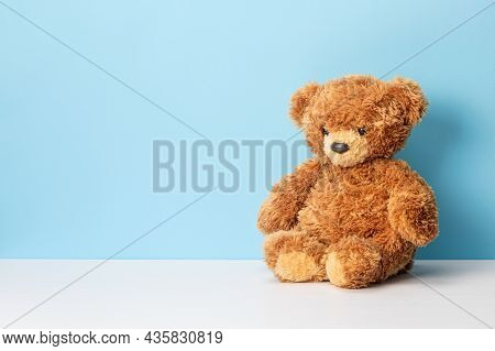 Teddy Bear Sits On A White Table And Blue Background. Template Copy Space For Text