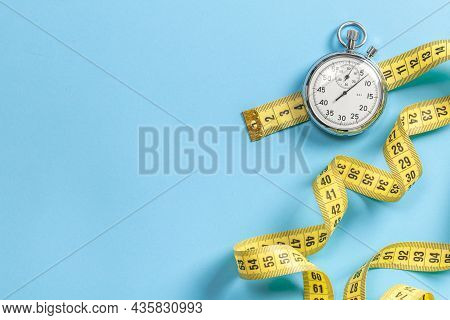 Fast Workouts. Yellow Measuring Tape Meter And Stopwatch On A Blue Background. Template Copy Space F