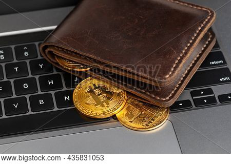 Bitcoin Wallet. Wallet With Gold Coins On The Laptop Keyboard