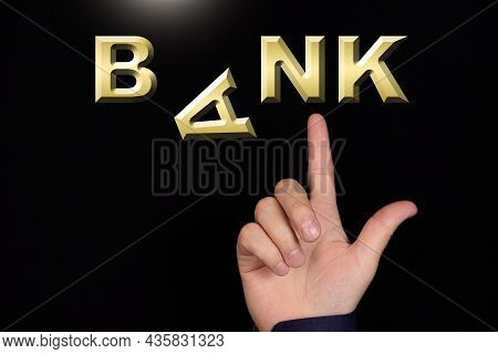A Finger Points To The Word Bank, Made Of Miniature Three-dimensional Letters, With The Letter A Fal