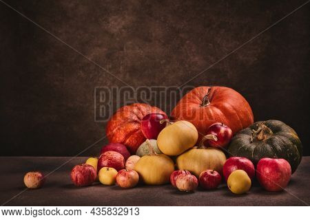 Thanksgiving background. Festive still life with pumpkins and apples on dark brown background with copy space. Happy Thanksgiving  day, autumn harvest or Halloween.