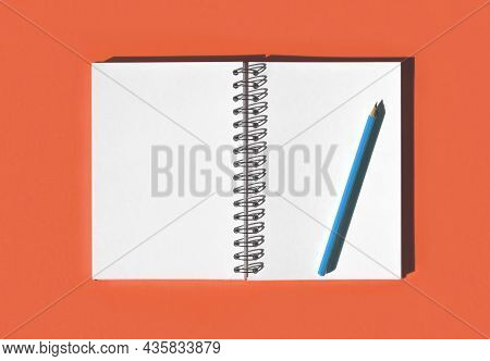 Notebook With Pencil. School Notebook On Red Orange Background, Spiral Notepad On Table. Top View Of