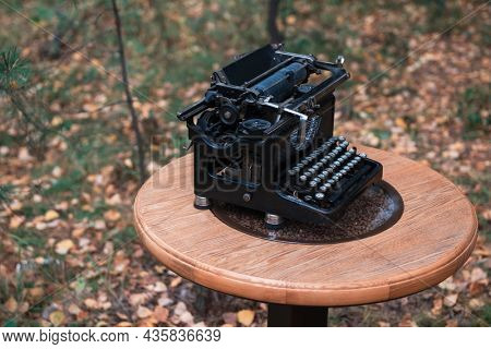 Vintage retro typewriters on the wooden table in the autumn forest background