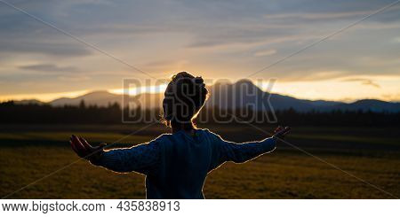 Young Woman Standing In Beautiful Nature At Sunset Meditating With Arms Spread Gently Lit By The Set