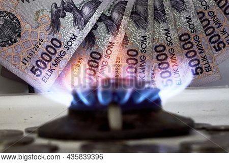 Burning Gas Stove Burner And Uzbek Money - Sum Banknotes. Pay For Natural Gas, Bill, Tariff. Growing