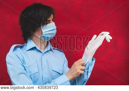 Young Man In A Medical Mask Puts On Protective Gloves On A Red Background. Male Portrait. Virus Prot