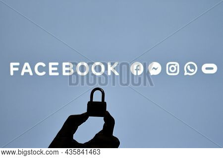 Tashkent, Uzbekistan - 7 October 2021: Silhouette Of A Person Hand Holding A Padlock Over Facebook L