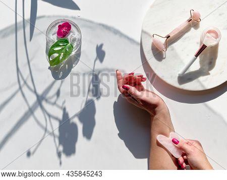 Hand Massage, Lymph Drainage With Pink Quartz Gua Sha Stone. Moisturizing Cream On Marble Plate. Exo