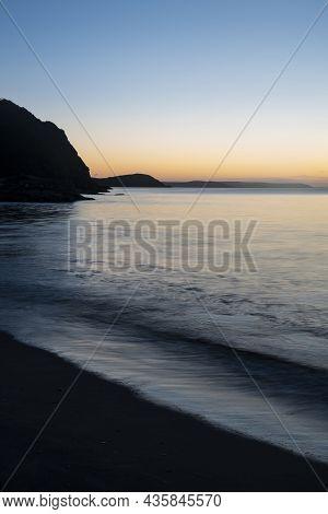 Beautiful Sunrise Over Pentewan Sands In Cornwall With Pastel Sky And Long Exposure Ocean