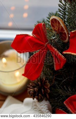 winter holidays, new year and decorations concept - close up of christmas wreath and candle on window sill at home