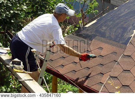 The Roofer On The Roof Of The Gazebo Is Preparing To Lay The Tiles From The Bottom Up To The Ridge