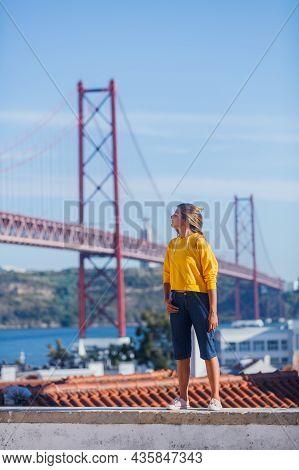 Portugal Tourist Attractions Concept. Attractive Brunette Girl Und 25th April Bridge In Lisbon