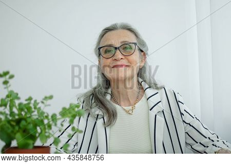 Senior Grey Haired Businesswoman In Striped Jacket With Eyeglasses Is Working In Her Office Sitting