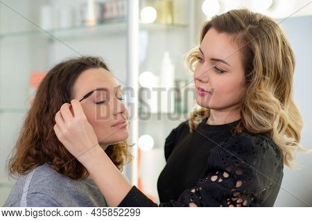 Makeup artist combs  eyebrows in a woman with an eyebrow brush. Make-up artist in beauty studio doing makeup for beautiful girl. Adult woman in a beauty salon on care procedures at a cosmetologist