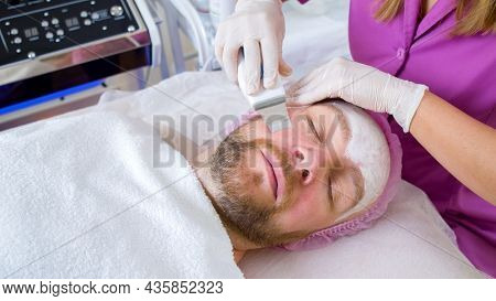 Beautician using electrical impulses for facial procedures.  Man in a spa salon on cosmetic procedures for facial care. Adult man receiving facial microcurrent treatment at spa salon.