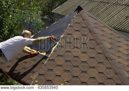 The Roofer Fixes The Hardboard With A Screwdriver