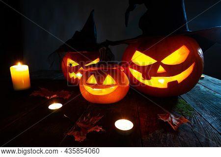 Still life of Halloween pumpkin lanterns pumpkins and hats decoration in candle light