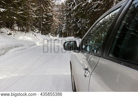 Driving a car on a snowy winter mountain road in the alps