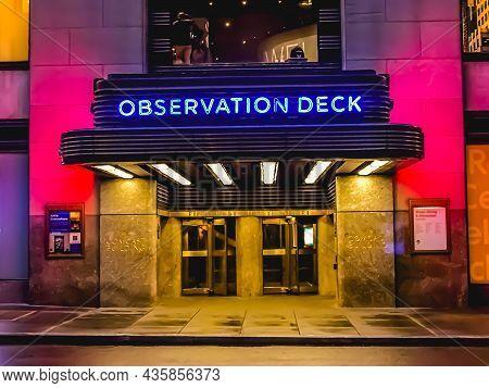 Exterior Entrance Of 30 Rockefeller Plaza Comcast Building At Night With Blue Observation Deck Neon