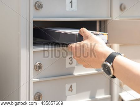 Mail Man Delivering Small Parcel In Mailbox By House Number, Selective Focus. Person's Hand Holding