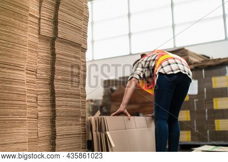 High Stack Of Card Board Paper Box With Industrial Worker Doing Arrange Cardboard In Factory Area. H