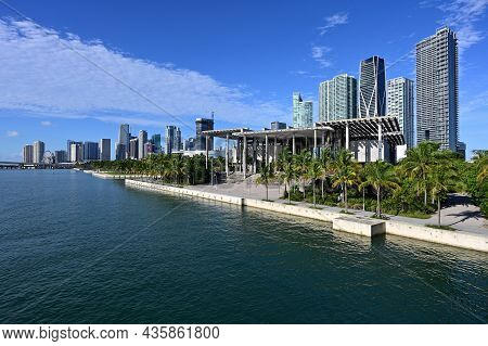 City Of Miami, Florida Skyline Reflected In Biscayne Bay Under Sunny Summer Cloudscape.