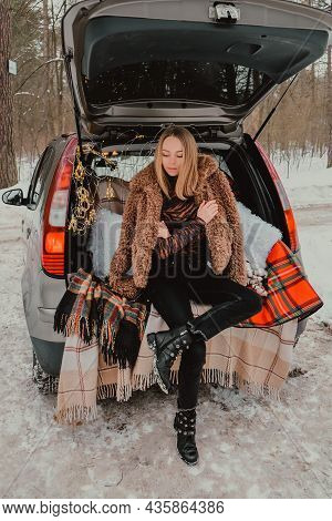 Blonde Woman Wrapped In Blanket In Trunk Car. Travel In Winter. Car Decorated With Festive Christmas