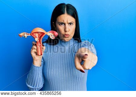 Beautiful brunette woman holding anatomical model of female genital organ pointing with finger to the camera and to you, confident gesture looking serious