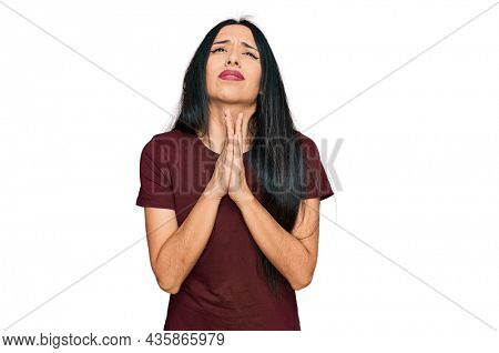 Young hispanic girl wearing casual t shirt begging and praying with hands together with hope expression on face very emotional and worried. begging.