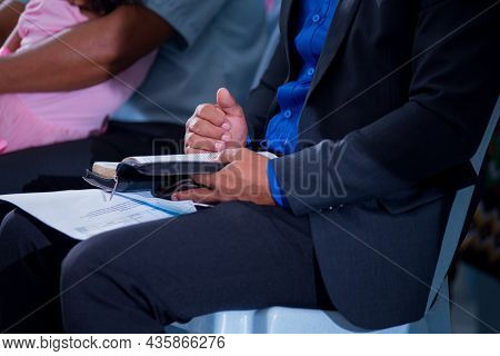 A Man Dressed-well, Sitting On Chair, Opening The Bible And Reading In The Church.