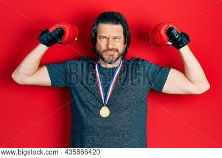 Middle age caucasian man wearing first place medal on boxing competition skeptic and nervous, frowning upset because of problem. negative person.