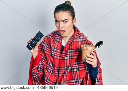 Young caucasian girl wearing blanket holding television remote control and ice cream in shock face, looking skeptical and sarcastic, surprised with open mouth