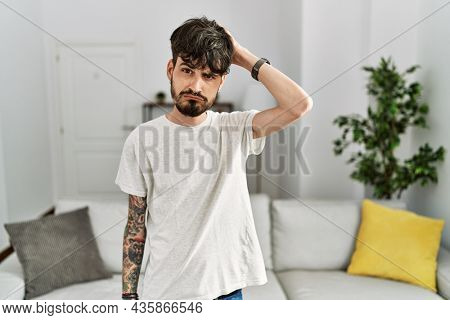 Hispanic man with beard at the living room at home confuse and wondering about question. uncertain with doubt, thinking with hand on head. pensive concept.