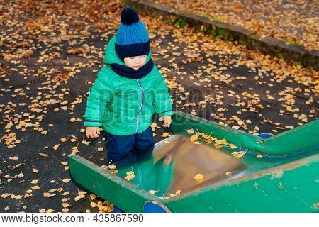 Lonely Child Standing Near Slide On Outdoor Playground. Sad, Alone Kid In Autumn Park.