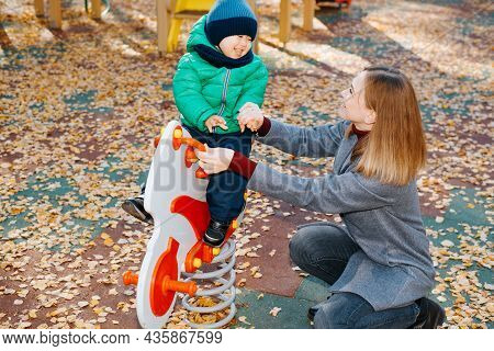 Happy Family, Mom And Child Playing On Playground, Laughing Kid Rides Toy Horse. Smiling Young Mothe