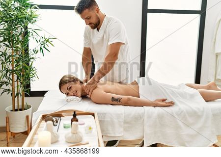 Young caucasian woman at physiotherapy clinic getting muscle massage by professional therapist. Physiotherapist man doing rehabilitation treatment to client