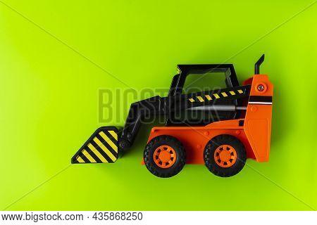 Orange Toy Loader On Green Background, Mini Loader, Toy Industrial Car, Plastic Front Wheel Loader.