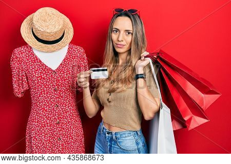 Beautiful hispanic woman holding shopping bags and credit card relaxed with serious expression on face. simple and natural looking at the camera.