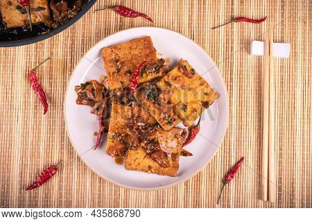 Fried Tofu With Onions And Hot Pepper Sauce - Portion On A Plate With Chopsticks, Top View