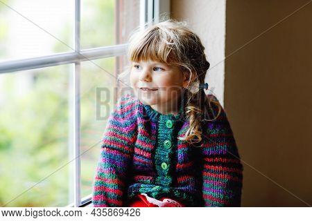 Little Girl Sitting By Window. Preschool Child Wear Cozy Self Knitted Wool Sweater. Toddler Watching