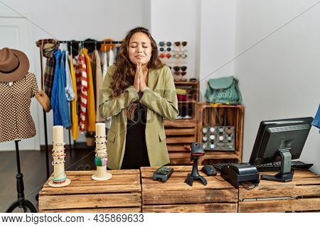 Beautiful hispanic woman working at fashion shop praying with hands together asking for forgiveness smiling confident.