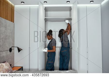 Young Multiracial Man And Woman In Work Clothes Mounting Metal Hanging Rails Inside Large White Bedr
