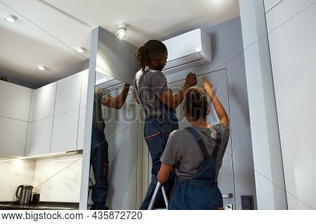 Back View Service Company Workers Installing Air Conditioner. Woman Senior Technician Advising Her M