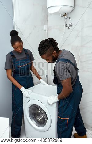 Young African Man And Woman, Technicians In Gloves And Overalls, Pulling Washing In Bathroom. Servic